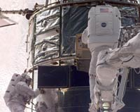 During the second spacewalk Claude Nicollier, ESA, (right) is inserting the Fine Guidance Sensor into Hubble. Michael Foale (left) is assisting.