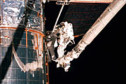 Astronauts Lee and Smith repairing parts of Hubble's insulation.