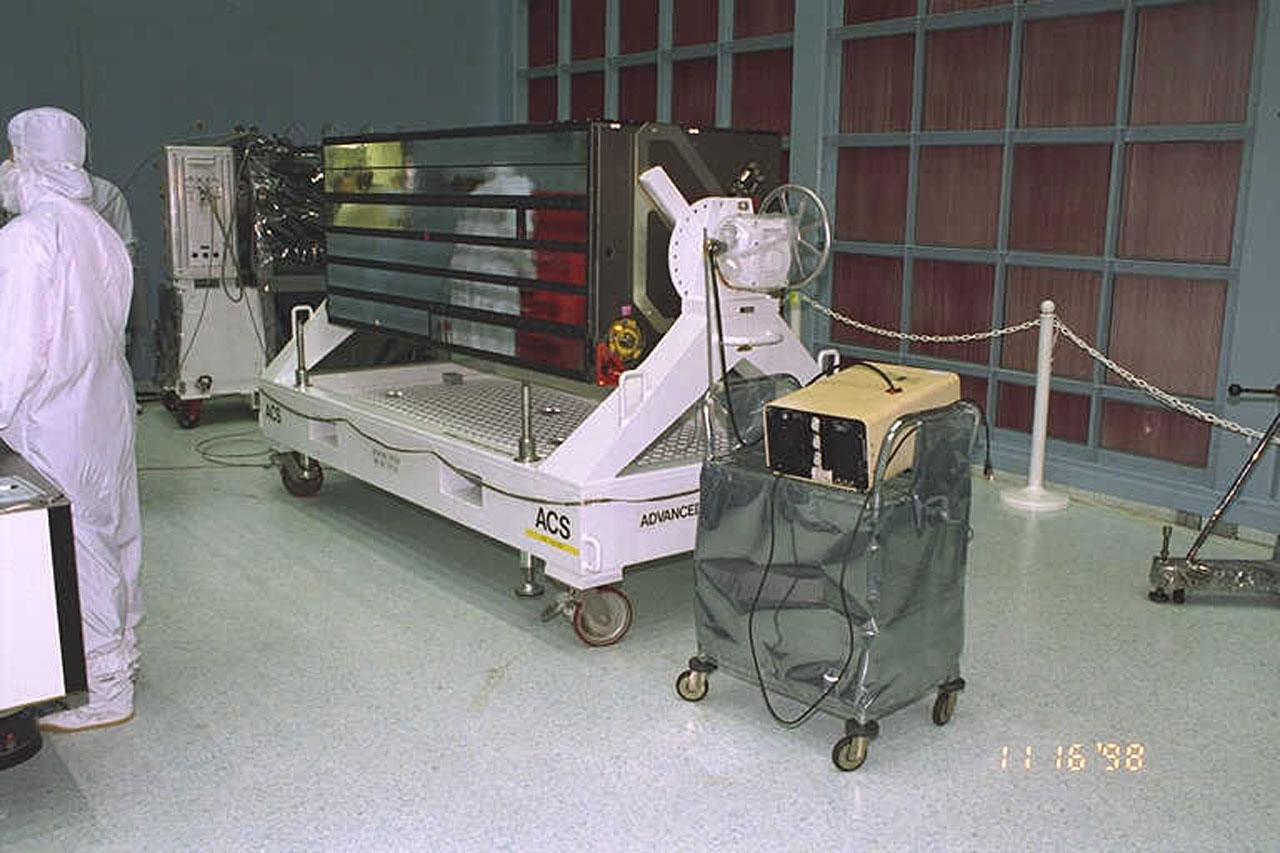 Technicians working with the ACS instrument in a clean room environment.